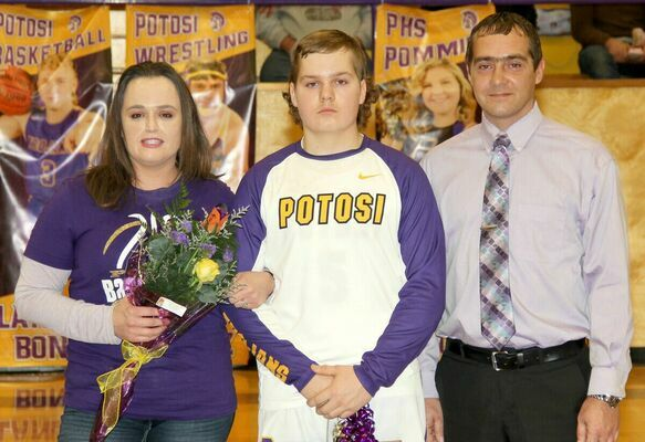 SENIOR TROJAN CORY EMILY has played 4 years of basketball and baseball for Potosi and escorted his mom and dad, Heather and Cory Emily at the Senior Night Celebration on Friday at the P.H.S. gym.