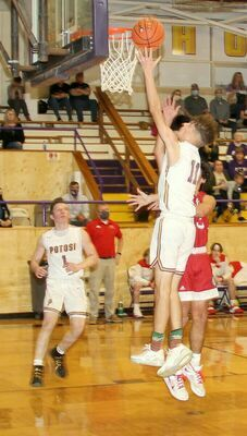 FAST BREAK FOR PEPPERS - Potosi's #11 Malachi Peppers lays up two points for the Trojans against the St. Clair Bulldogs as #1 Ty Mills watches the play.