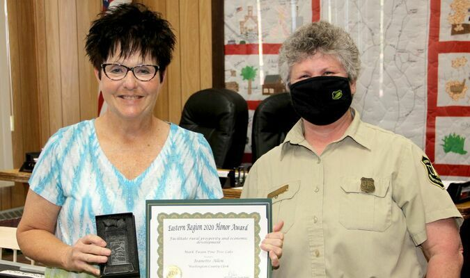 EASTERN REGION HONORS FROM FOREST SERVICE – Becky Ewing, District Ranger for Mark Twain National Forest, Potosi/Fredericktown presented Washington County Clerk Jenny Allen a certificate and a laser engraved glass award on Monday, May 3rd, 2021 at the Washington County Commission meeting at the Courthouse. Ranger Ewing said Mrs. Allen was instrumental in the development and successful installation of a wildfire suppression system at the Pine Tree Lake subdivision on Highway 8 West of Potosi. Mrs. Allen was credited with taking care of project data and financial records for the installation of the dry hydrants.