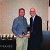 Cameron Insurance Companies President Brad Fowler, right, presents the President's Award plaque to Brad Sharpe.