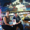 "Al Beck presents Canton Public Library's Carol Hill with a copy of ""WHO OWNS AL'S POETIC BONES?"""