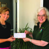 Lewis Street Playhouse president Dell Ann Janney receives a grant check from Canton Area Arts Council Board president Carol Mathieson.
