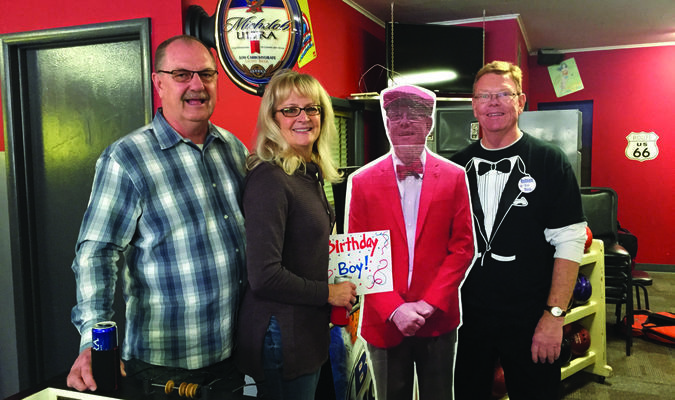 Ralph Martin, Karen McFarland and Craig Redmon stand by a cardboard cutout of Redmon. Craig was celebrating his birthday at his bowling tournament.
