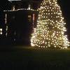 The tree all lit up with the mansion in the background.