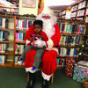 Sam Johnson sits patiently on Santa's lap after he had told Santa what he would like for Christmas.