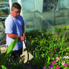 Justin Plant cares for blooming planters to be used at the Lewis County Fair Grounds.