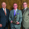 Craig Redmon, center, receives his Legislative Leadership Award from Vice President David Klindt, left, and CEO Barry Hart.