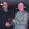 """Ralls County Presiding Commissioner Wiley Hibbard presents Steve Whitaker with a plaque """"to commemorate his 12 years of service and dedication to the citizens of Ralls County."""" The presentation took place at the County Christmas Meal heldat the New London First Chrsitian Church and attended by all county employees who wished Whitaker well in his future endeavors."""