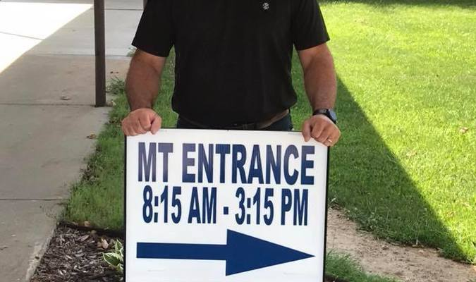 Mr. Howell stands behind the sign that it directs all students and visitors to the JH office entrance on the other end of the building.