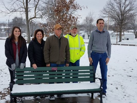Standing behind a snow covered bench are Devyn Campbell - Mark Twain Regional Council of Governments, Danette Henderson - Perry City Clerk, Don Huff - Perry Utility Superintendent, Wiley Hibbard - Ralls County Presiding Commissioner, Chad Williams - Mayor of Perry.