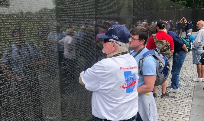 Danny Gibbons and his son, Daniel Gibbons search the Vietnam Memorial for names.