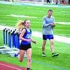 Maddy Ford competes in the 1600 while Devin Neff cheers for her. Both Ford and Neff finished in first place in the 1600 meter run.