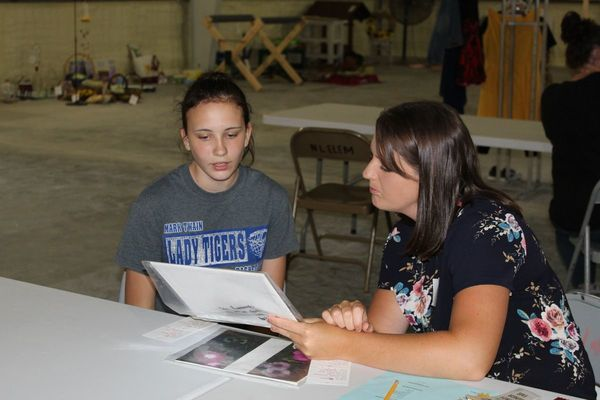 Rocky Point 4-H member, Julianne Kamrowski talks to a judge about her project.