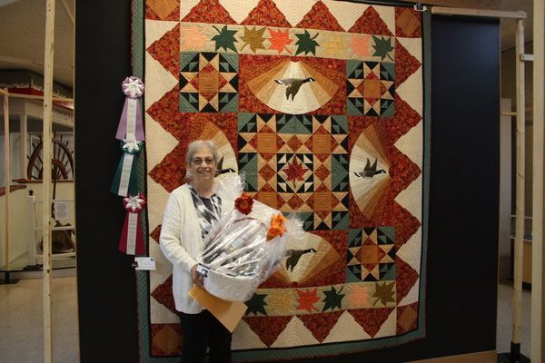 "Carol Wyss, winner of the Judge's Choice & the People's Choice with her quilt, ""October Morn."""