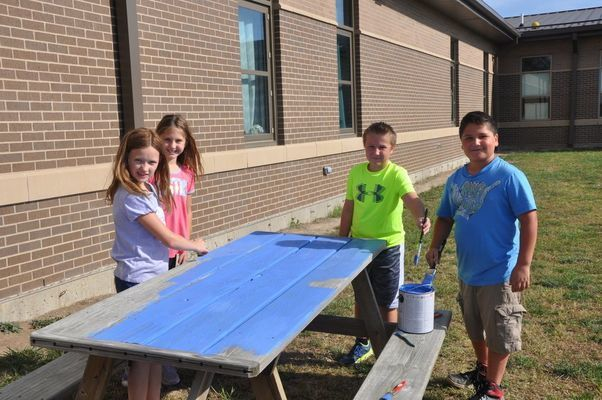 Miss Runyon's fourth grade students help to paint picnic tables on the school playground during their life skills class. Picture (l to r) are Billie Jo Resor, Madilyn Romig, Jorden Armour, and Joshua Miller. Painting tables with just one of the many service learning opportunities available for elementary students to participate in.