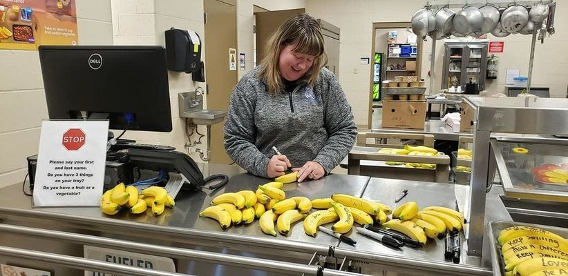 Ralls County RII Food Services' Director, Jeanna Camp, writing messages on bananas.