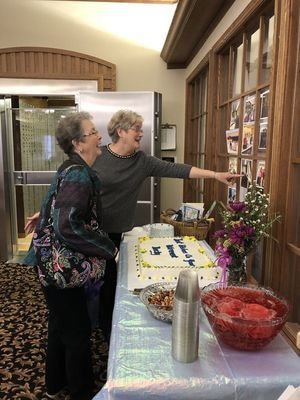 Becky Dunlap and Carol Kirtlink enjoy looking at pictures at Dunlap's retirement reception on Friday, December 6, at HNB in Perry.