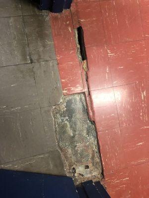 Asbestos tile in the doorway of one classroom shows the deterioration of both hallway and classroom floor tiles.