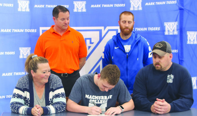 Ryan Spoonhower is pictured after signing a letter of intent to play football for MacMurray College in Jacksonville, Illinois. Pictured with him are his parents Paula and Scott Spoonhower and MTHS coaches Karl Asbury and Jared Akright.