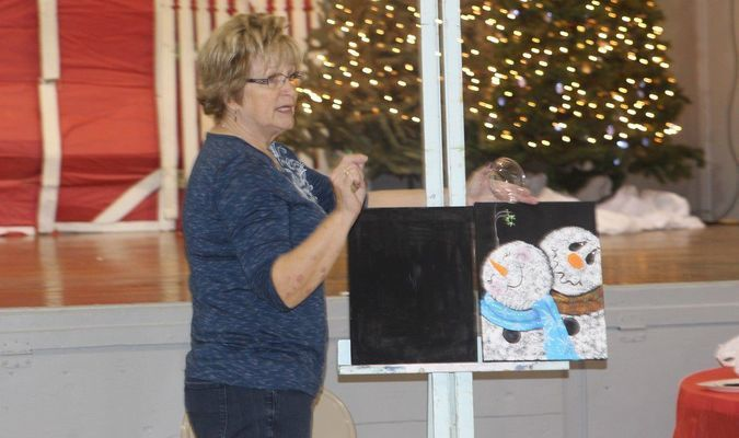 Kaye Egbert explains how to use the round brush to create the snow for the snowman's head and body at the December 7 class at the Old School Marketplace.