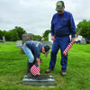 Teachenor Post 376 American Legion Post Commander Gale Buckman looks on as his grandson Jace McWilliams places a flag at a grave of a veteran on Thursday, May 21. They were just two of a group of people who placed flags in the Shelbina Cememtery and St. Mary's Catholic Cemetery.                        Photo by Thad Requet, Shelbina Weekly