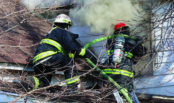 Pictured above are two fire fighters from the Shelby Community Fire Department battling a house fire at 609 Dickerson Monday afternoon. They assisted the Shelbina Fire Protection District.                        Photo by Mark Requet, Shelbina Weekly