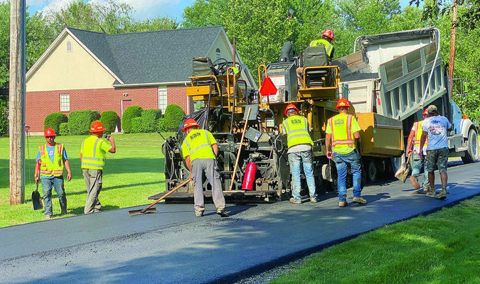 Workers from Emery Sapp & Sons are pictured above laying down a new surface on West Wood Street in Shelbina on Friday evening. This is part of the street improvement project for 2020. 			Photo by Mark Requet, Shelbina Weekly