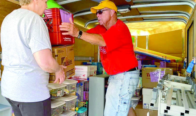 Approximately 40 students and 40 adults from the communities helped pack things from Clarence and Shelbina Elementary schools out to the new South Shelby Elementary Monday morning. Pictured above is Frank Ewart handing things to his wife Barb to take into the new school.