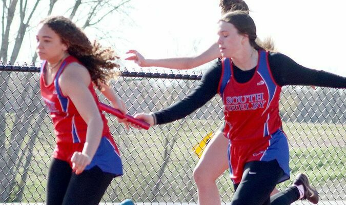 Madison Walker takes the baton from Kaylee Gaines during the Cansippi Relays at Highland High School on Thursday, April 15. Both the Lady Birds and the Cardinals had strong showing at the meet.                        Photo by Thad Requet, Shelbina Weekly