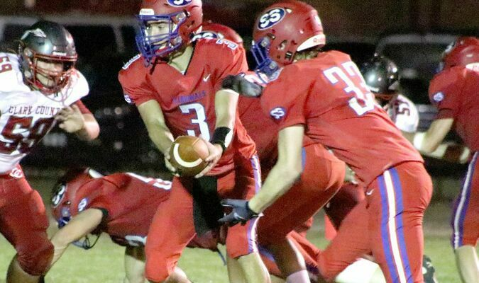 Quarterback Trey Countrymen hands the ball off to Kendal Hammond on Friday against Clark County. South Shelby won the game 35-20.                                     Photo by Mark Requet, Shelbina Weekly