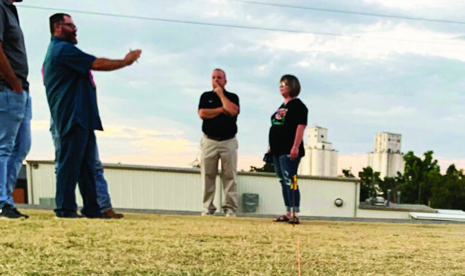 Carnegie school board president Christi Harrison and CPS Superintendant Eric Smith listen as Little League officials describe the measurements for the new field being planned behind the CHS softball complex.