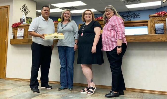 Michael Longhat, vice-president of the Carnegie Wildcat Education Endowment Fund, presents donuts to Bank of Commerce employees, Nicole Clark, Paula Watson and Kelly Williams.