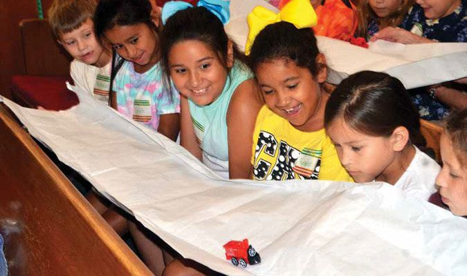 Children watch on with glee as a small toy train makes its way across a paper bridge that is stretched across their arms during last week's Vacation Bible School at the Carnegie Church of the Nazarene. In all, about 70 youngsters attended the week-long event.