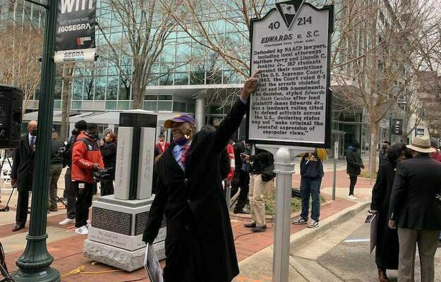 Rev. James Edwards touches a monument to protesters in the 1961 march on the State House.
