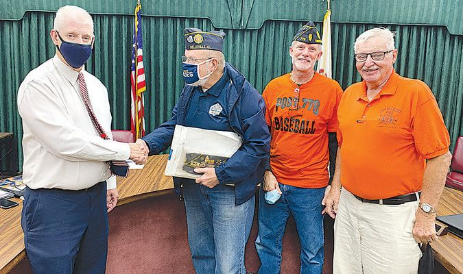 Trenton mayor Andy Weh shakes hands with Don Wallis, Illinois state chairman for American Legion Baseball, after Wallis announced Monday night that Trenton will be the host site for the 2022 American Legion Illinois Junior state tournament, in late July. With Weh and Wallis are Trenton American Legion Post 778 commander Dan Purdy, and Post 778 baseball general manager Pete Schumacher.