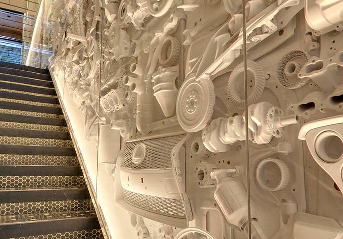 Heading upstairs to the second floor is an experience in itself: the staircase wall is lined with a cascading collage of 250 components from five different Lexus cars which were painstakingly arranged by Katayama before being painted a minimalist white.