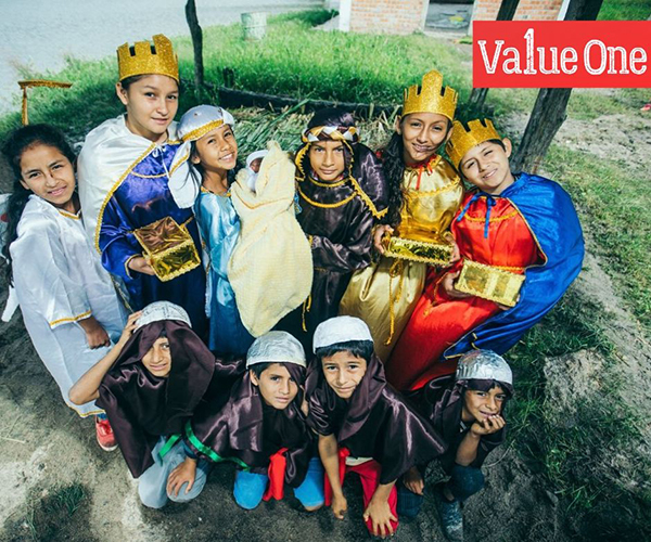 Kids dressed as characters from the nativity scene stand together and smile at the camera