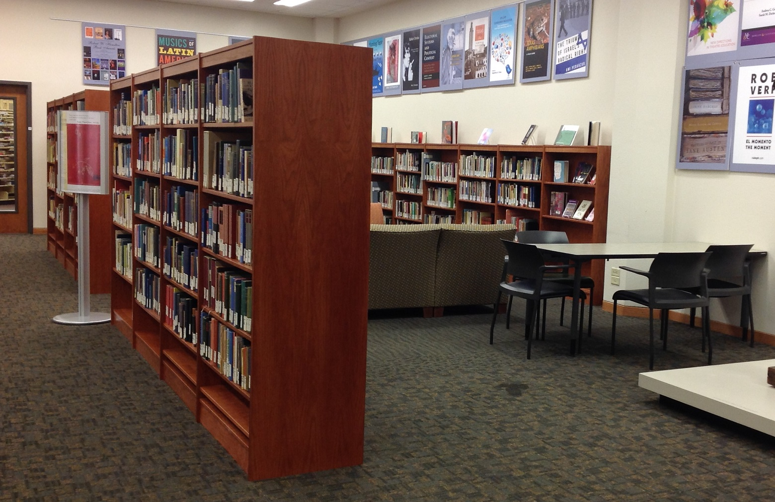 Image of the UT Poetry Center in the Perry-Castaneda's UFCU room. A group of bookshelves is in the forefront, with tables, chairs, couches, and more bookshelves in the background.