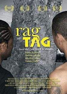 "Film poster for the movie Rag Tag. The film tagline says ""... love isn't black and white."" Inludes the image of two men standing in front of a tree."