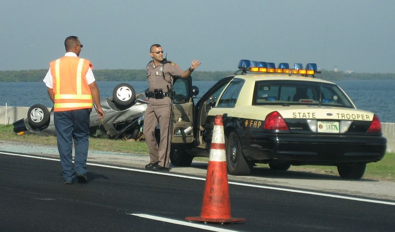 Image: State Trooper of the Florida Highway Patrol supervises cleanup of a multi-car wreck on the Howard Frankland Bridge in St. Petersburg Florida on the morning of June 9, 2006.