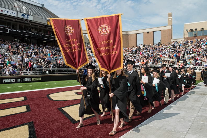 students marching into graduation