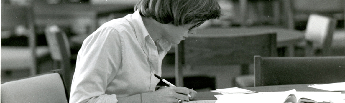 a student writing in a notebook in the library