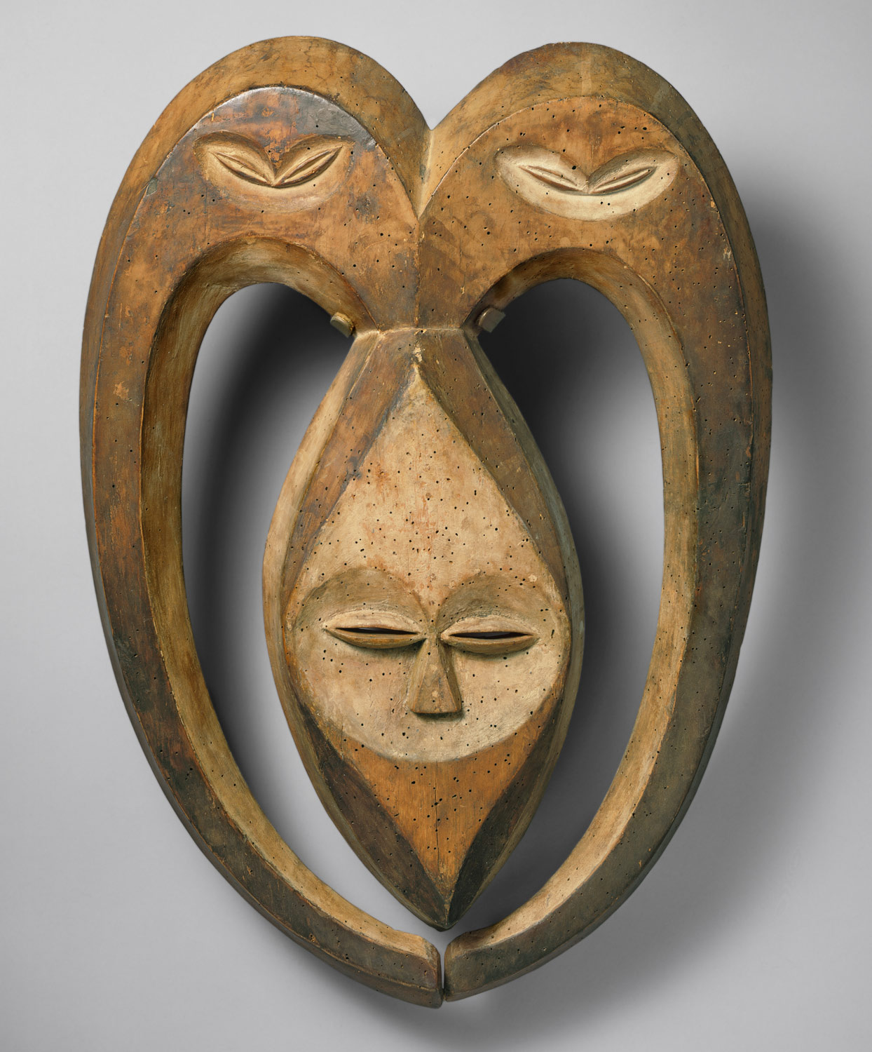 Beete Mask made of wood. The mask is heart-shaped and long, and the only facial features are the eyes and nose.