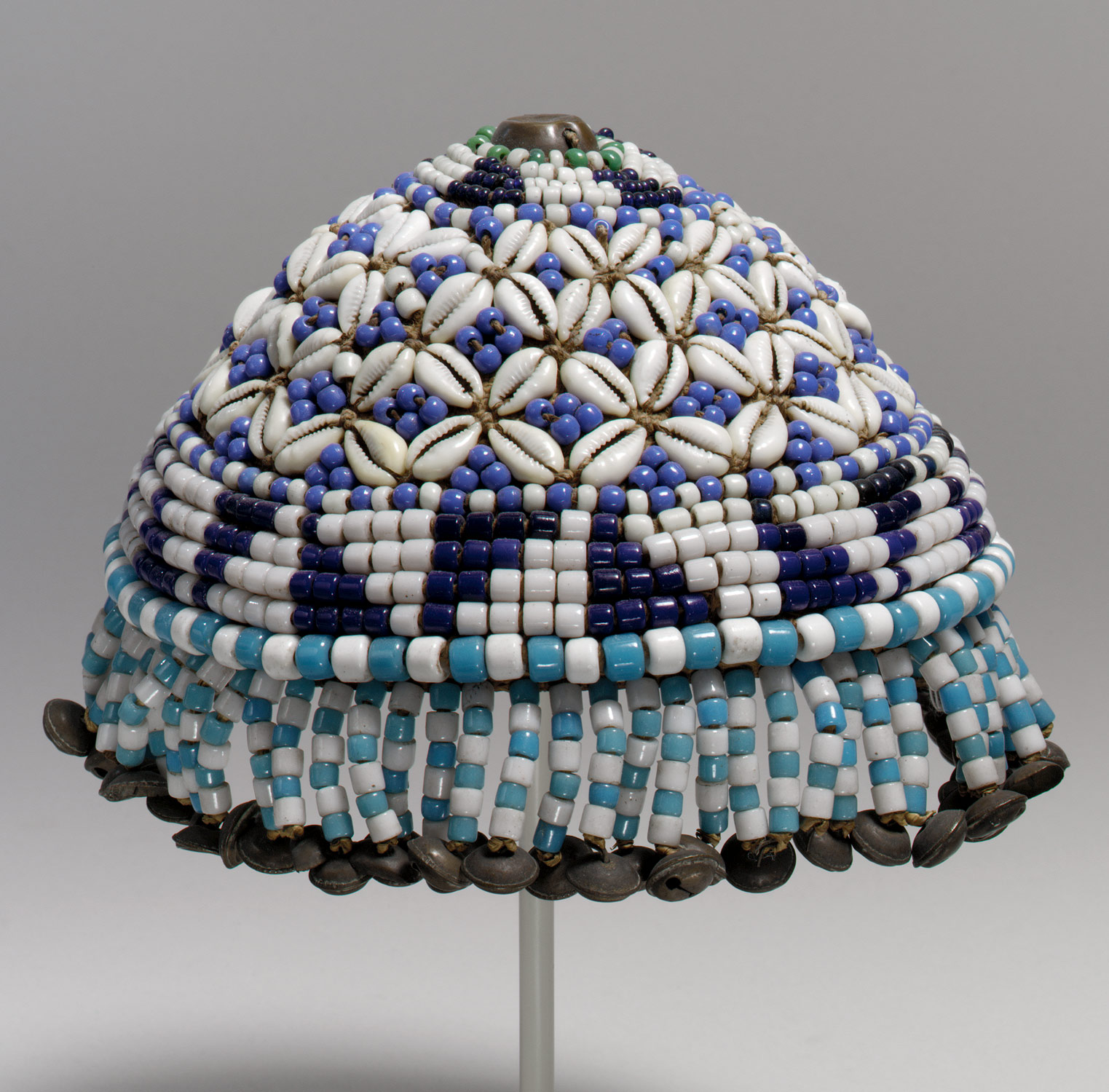 cap made of beads (white, light blue, medium blue, and dark blue) and cowry shells in a decorative pattern