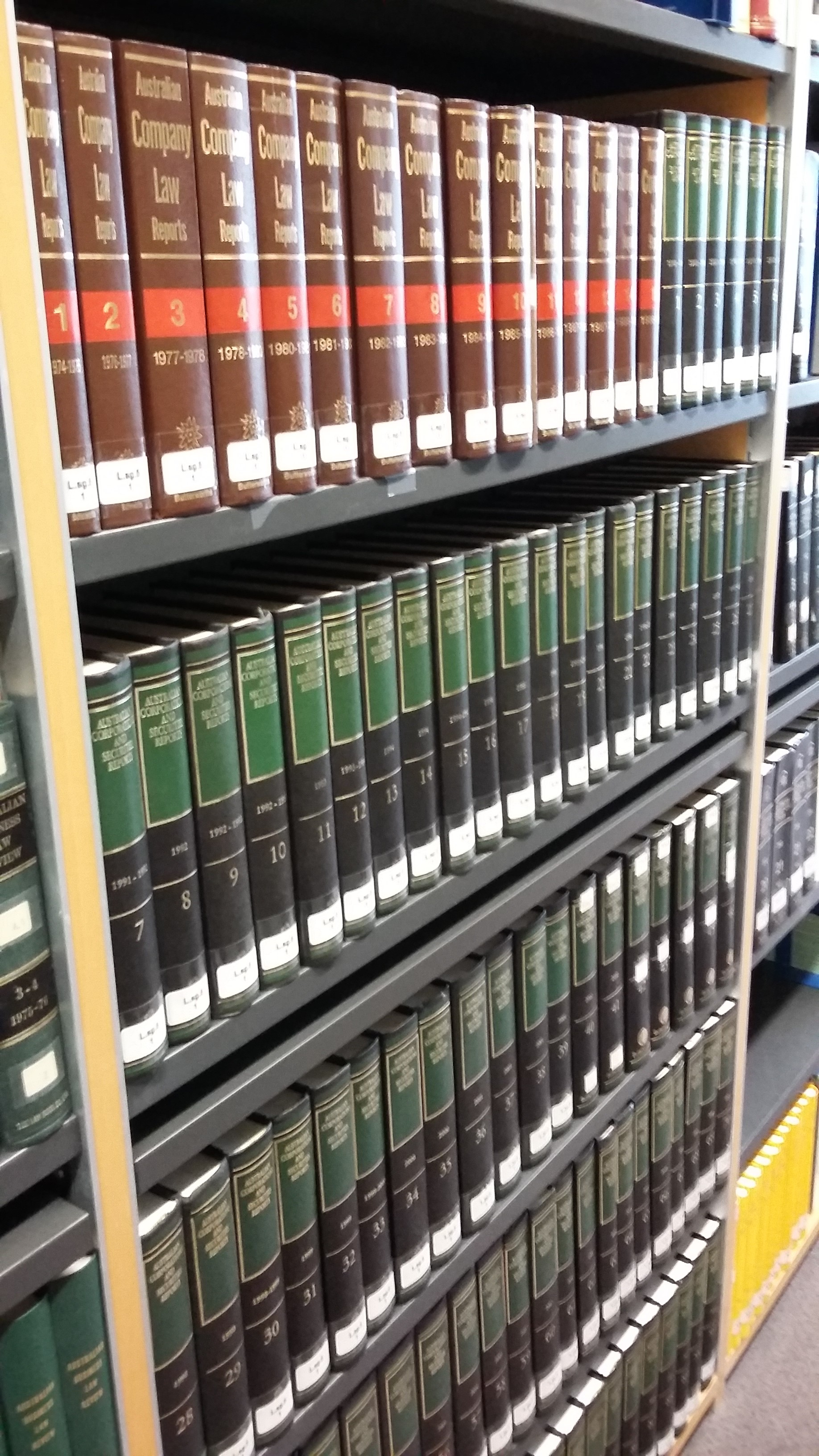 Photo of two sets of Australian law reports on shelves in the Squire Law Library. One set is brown and red - another is black and green.