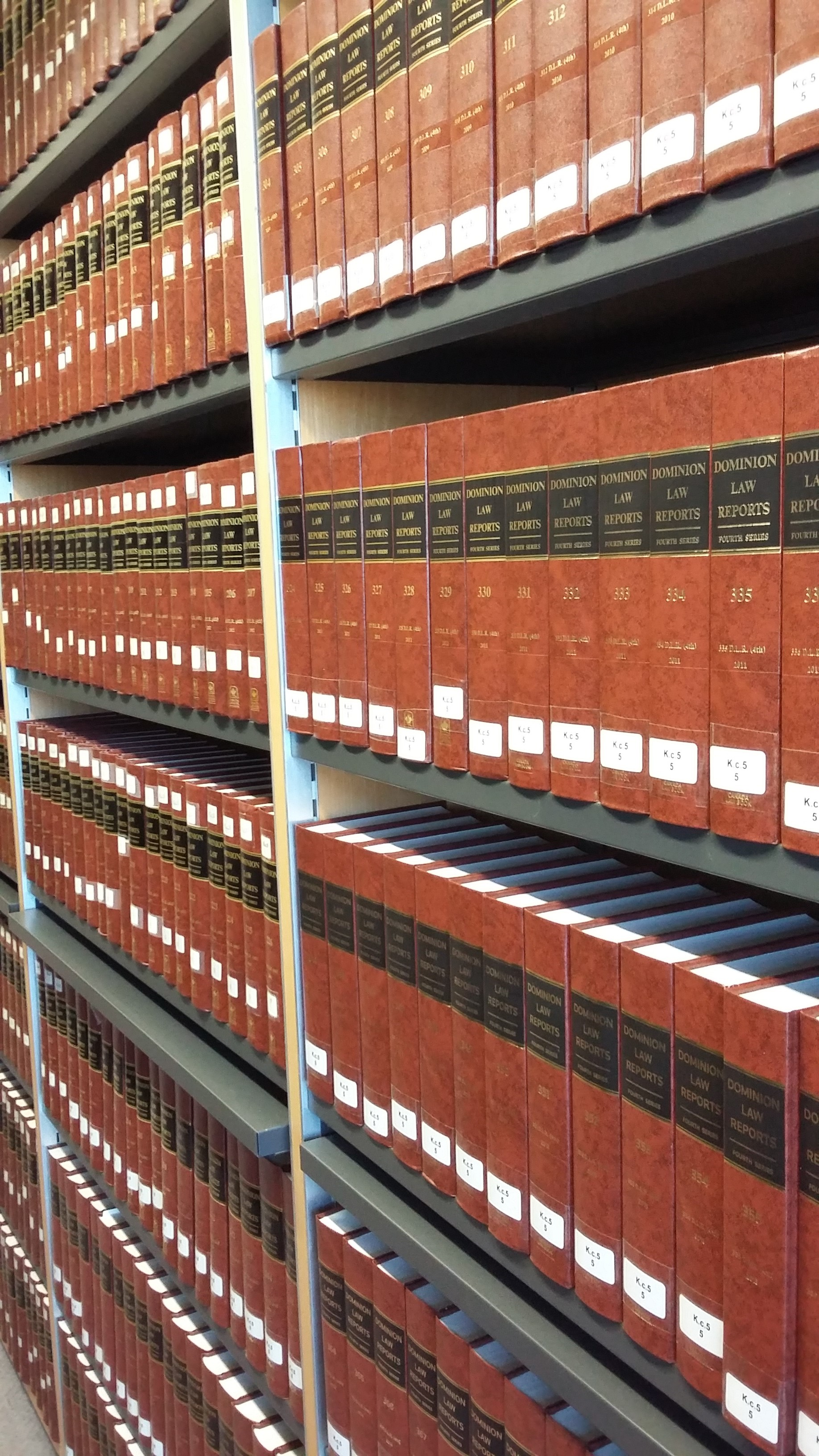 Photo of the three stacks of brown, black and gold volumes of the Dominion Law Reports on shelves in the Squire Law Library.