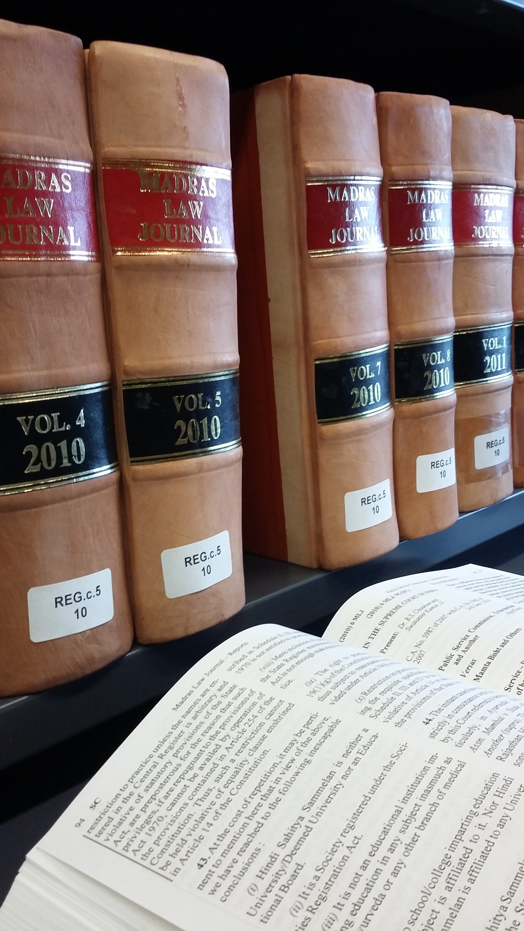 Picture of the Madras Law Journal on a shelf in the Squire Law Library with an open volume in front. The volumes look very grand in bound tan leather, with gold lettering on red and black backgrounds.