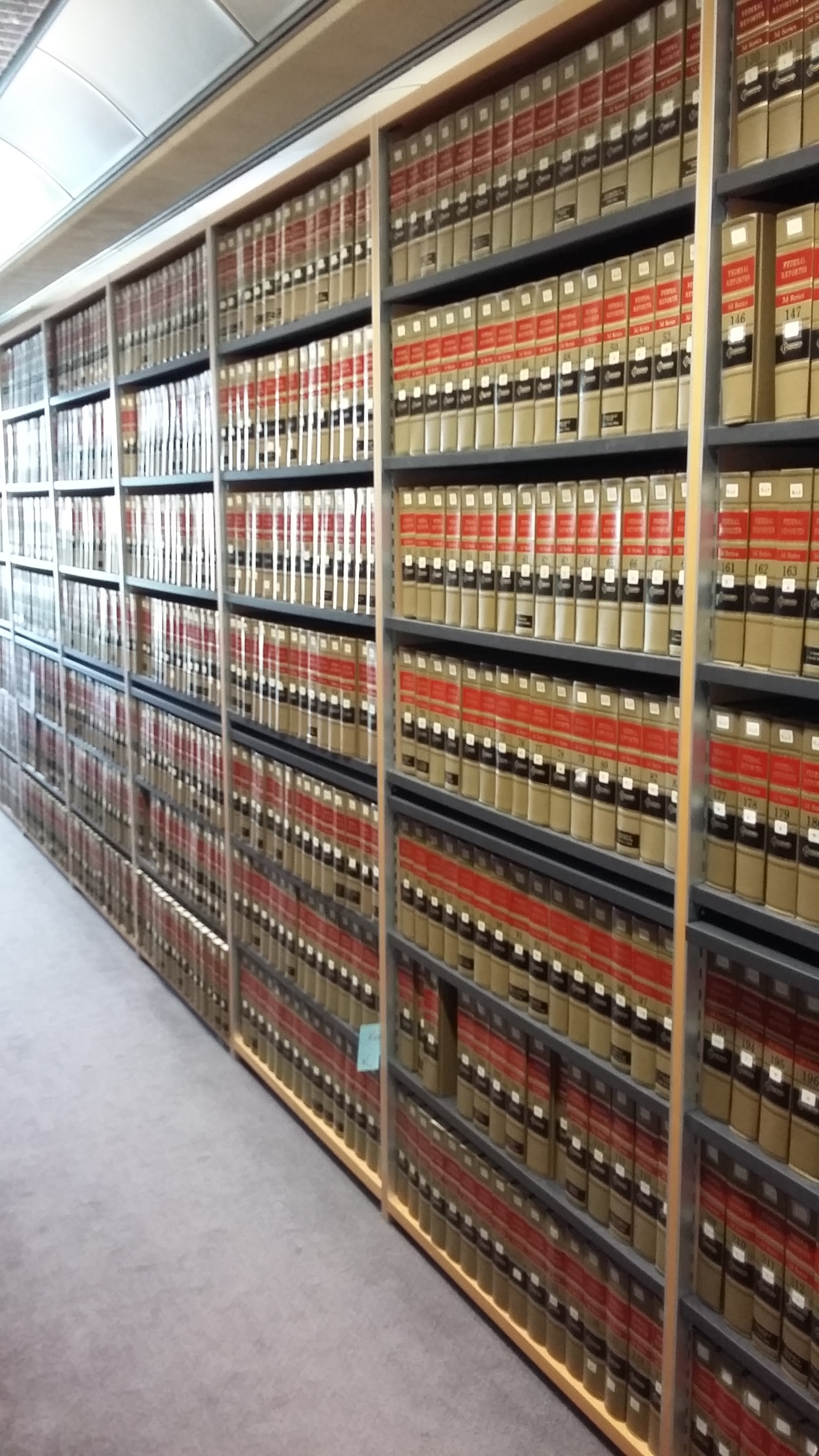 A view of stacks of American Reporter volumes, which are light brown, red and black, with gold lettering, on shelves in the Squire Law Library stretching into the distance.
