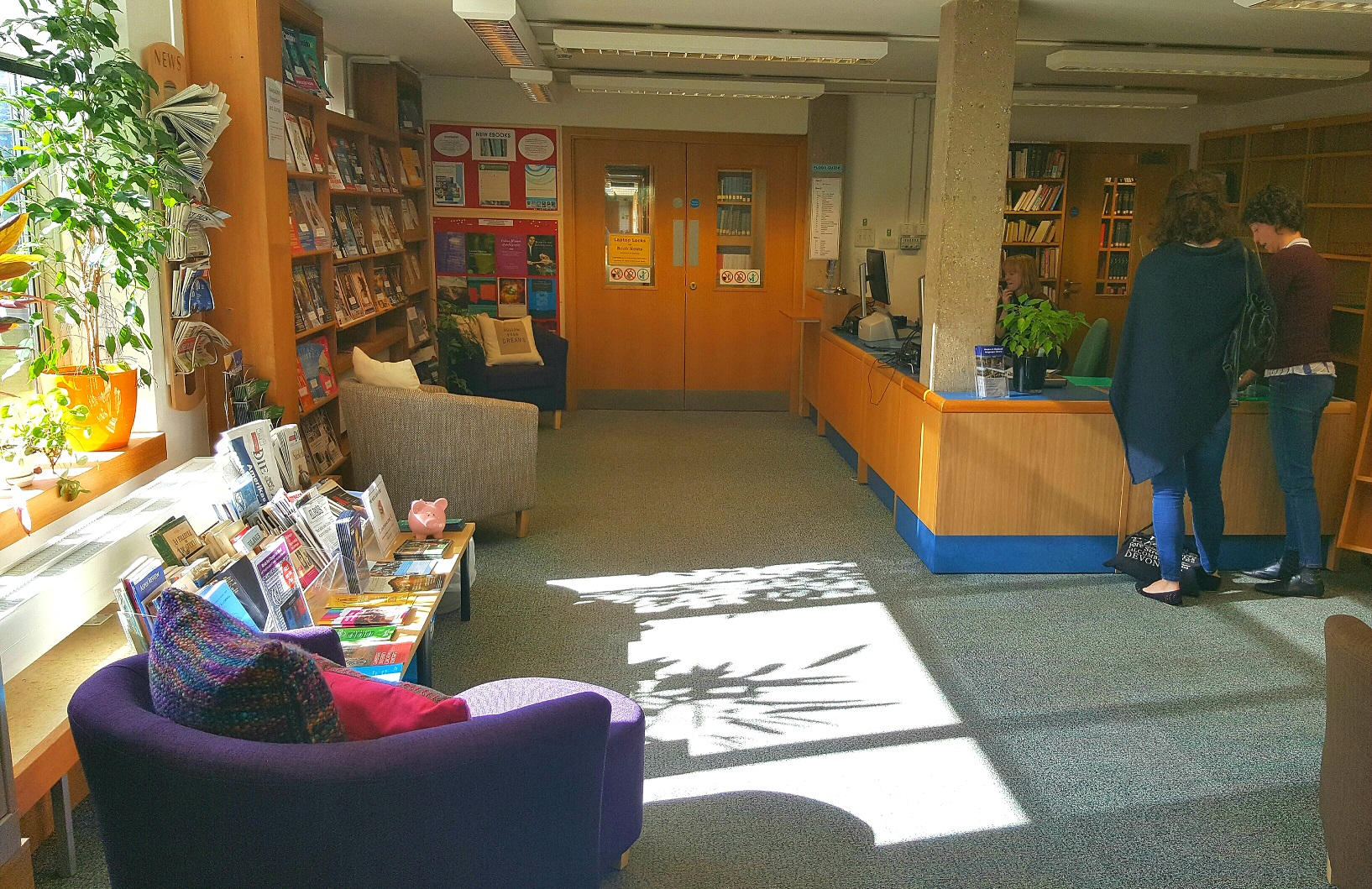 A colour photo of the MMLL Library lobby, with people standing next to the self-service machine