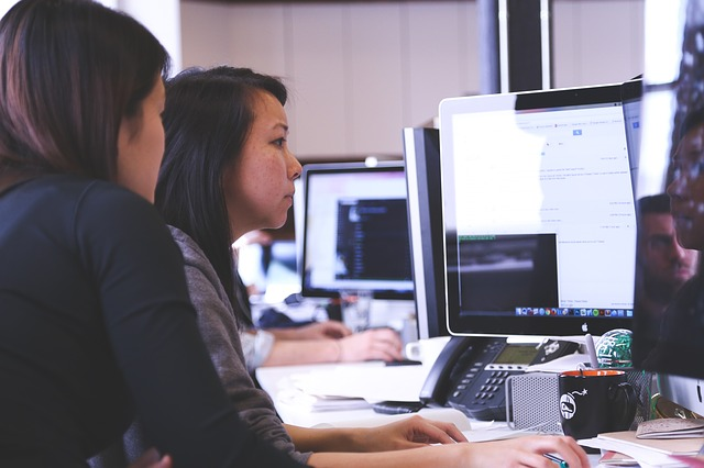 two females using a desktop computer